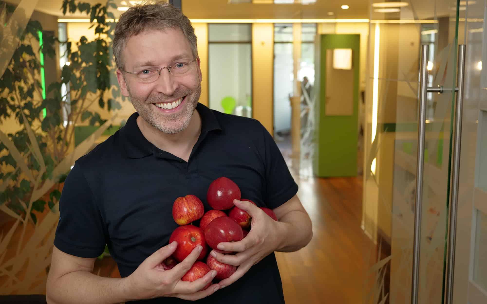 Unser Ziel ist Ihre lebenslange Zahn- und Mundgesundheit Dr. Wolfgang Gottwald lächelnd mit vielen roten Äpfeln in den Händen