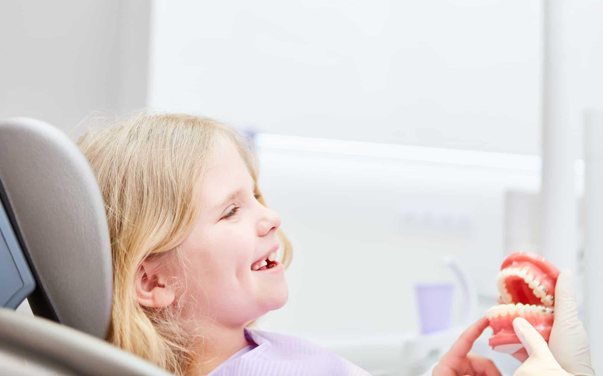 Unser Ziel ist Ihre lebenslange Zahn- und Mundgesundheit - auch in der Kinderprophylaxe - Fröhliches Mädchen als Patient sitzt angstfrei beim Zahnarzt